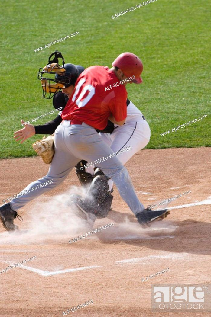 Stock Photo: Baseball player charging home plate.
