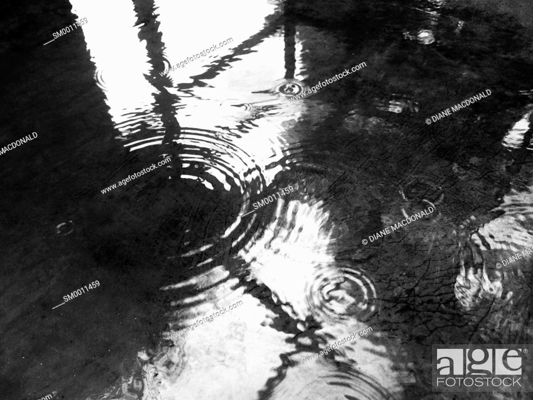 Imagen: A pool of water with ripples from raindrops and a window reflected.