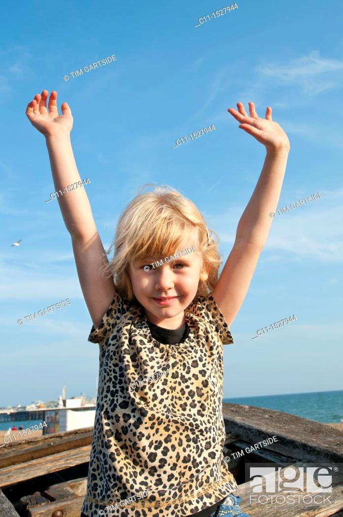 Stock Photo: young girl smiling and waving,Brighton, East sussex, England, Europe, UK.
