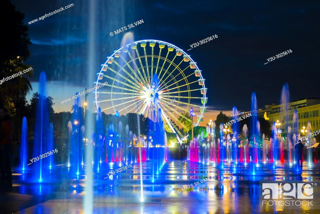 Stock Photo: Water Fountain and Ferris Wheel in Dusk in Nice in Provence-Alpes-Côte d'Azur, France.
