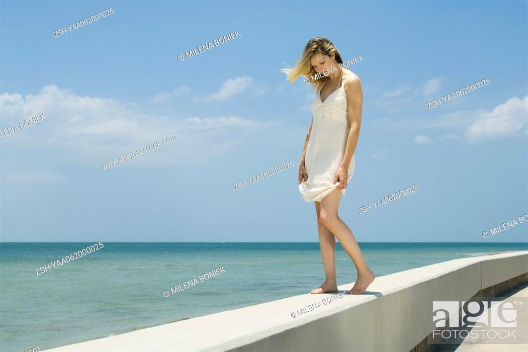Stock Photo: Young woman in sundress standing on low wall beside sea, eyes closed.