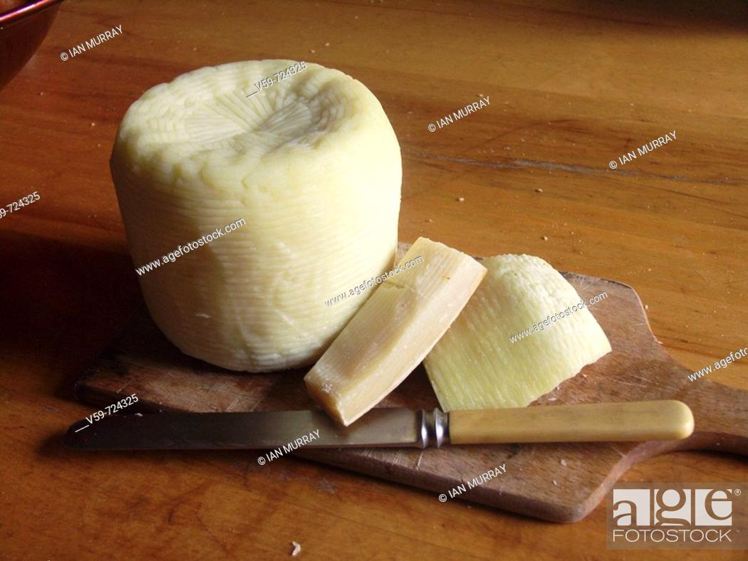 Stock Photo: Traditional soft cheese on cheeseboard with knife on wooden kitchen table, Sicily, Italy.