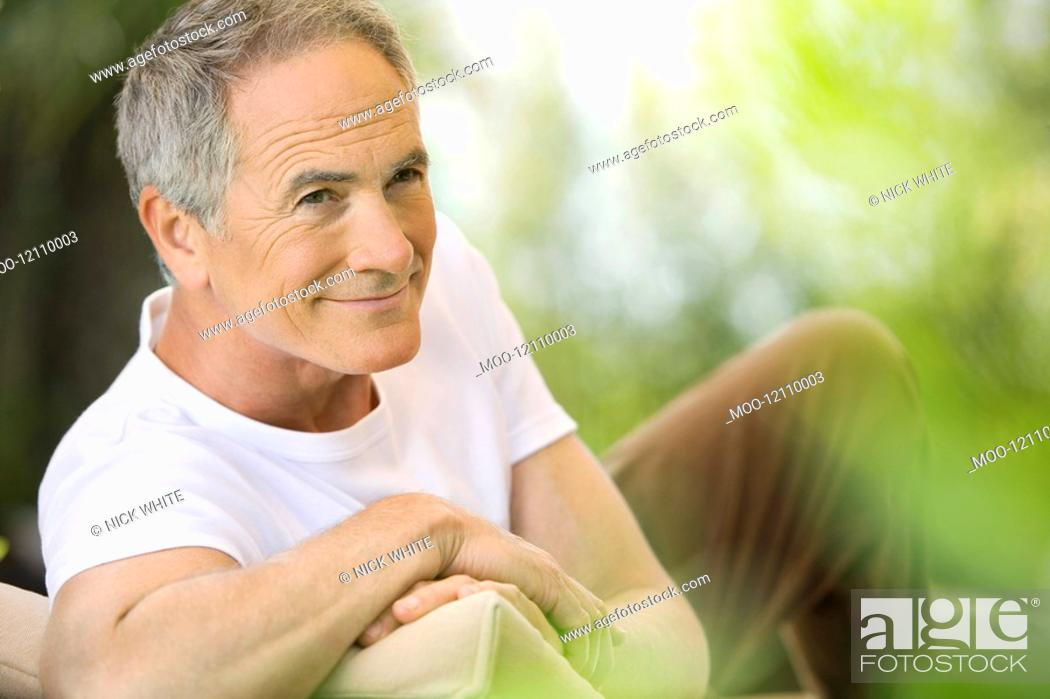 Stock Photo: Middle-aged man reclining on deck chair in garden.