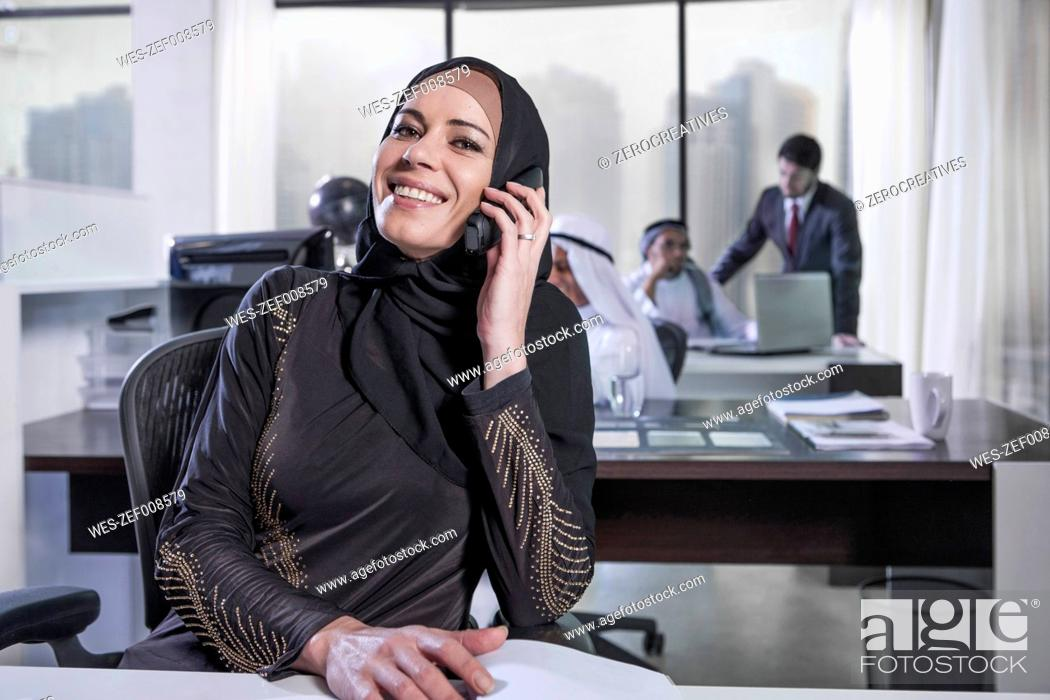 Stock Photo: Middle Eastern businesswoman in office talking on the phone.