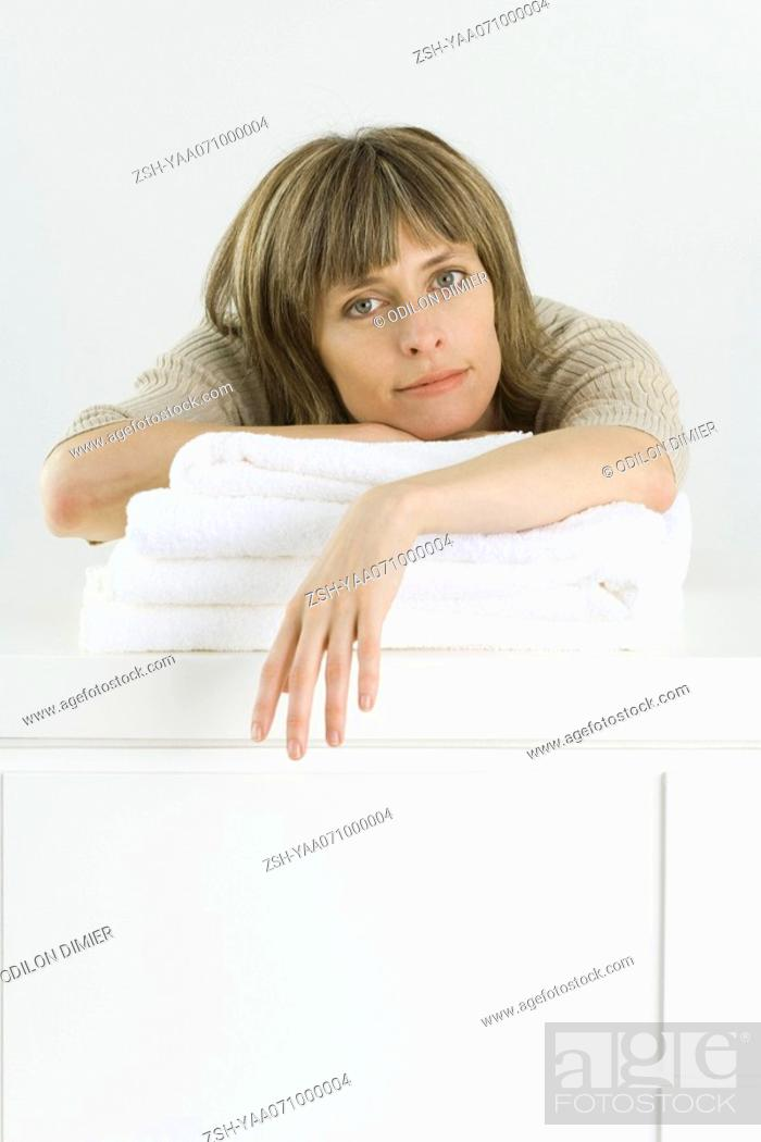 Stock Photo: Woman leaning over stack of towels on counter, looking at camera.