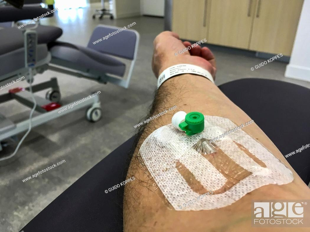 Stock Photo: Tilburg, Netherlands. Infusion Needle inside a patient's arm during a visit to at the hospital's emercency room.