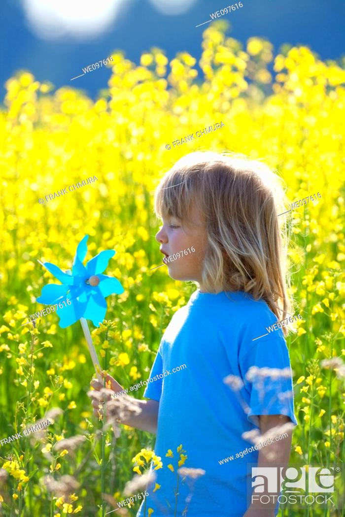 Stock Photo: boy with long blond hair holding pinwheel in canola field.