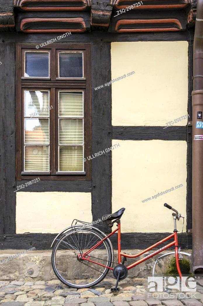 Imagen: Broken and abandoned bicycle in front of historic half-timbered architecture in Hoelle Alley in the Old Town of Quedlinburg, Saxony-Anhalt, Germany.