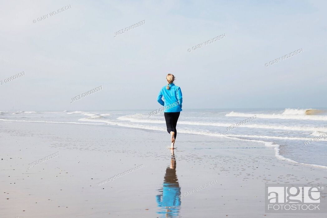 Stock Photo: Belgium, Flanders, woman jogging on the beach at low tide.