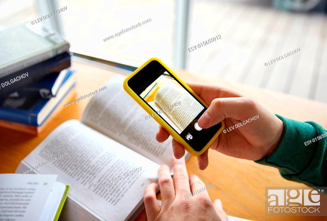Stock Photo: people, education, technology and exam concept - close up of student hands with smartphone taking picture of books page and making cheat sheet in school library.