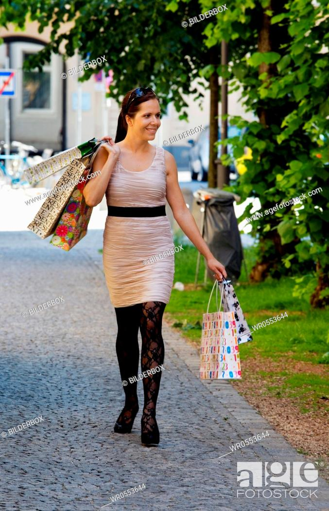Imagen: A young woman shopping with many shopping bags.