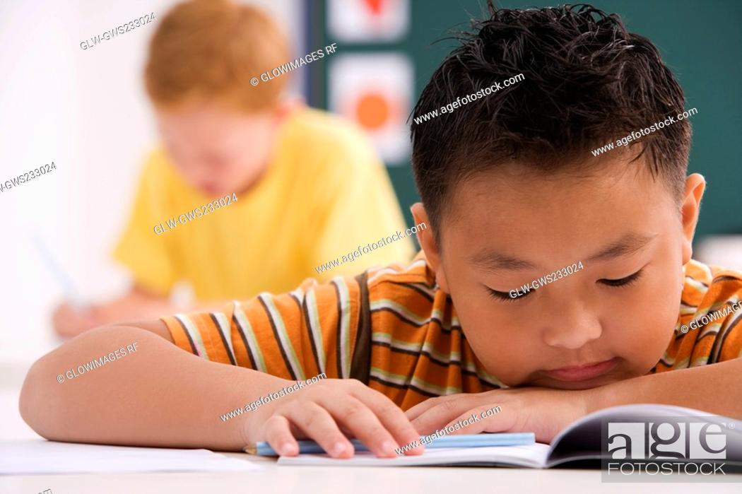 Stock Photo: Close-up of a schoolboy reading a book in a classroom.