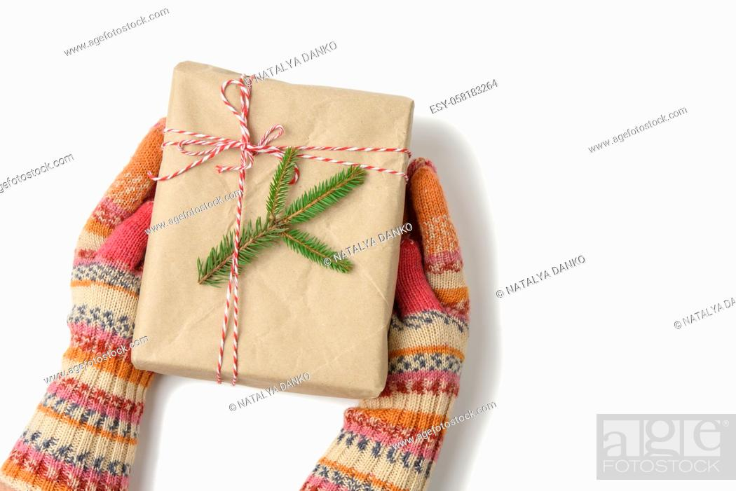 Stock Photo: female hands in knitted mittens hold a box wrapped in brown paper and tied with a rope on a white background, top view.