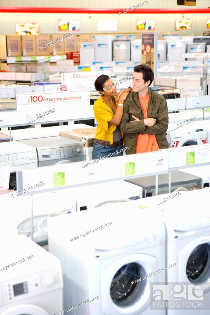 Stock Photo: Couple shopping for appliances, man with arms crossed, smiling.