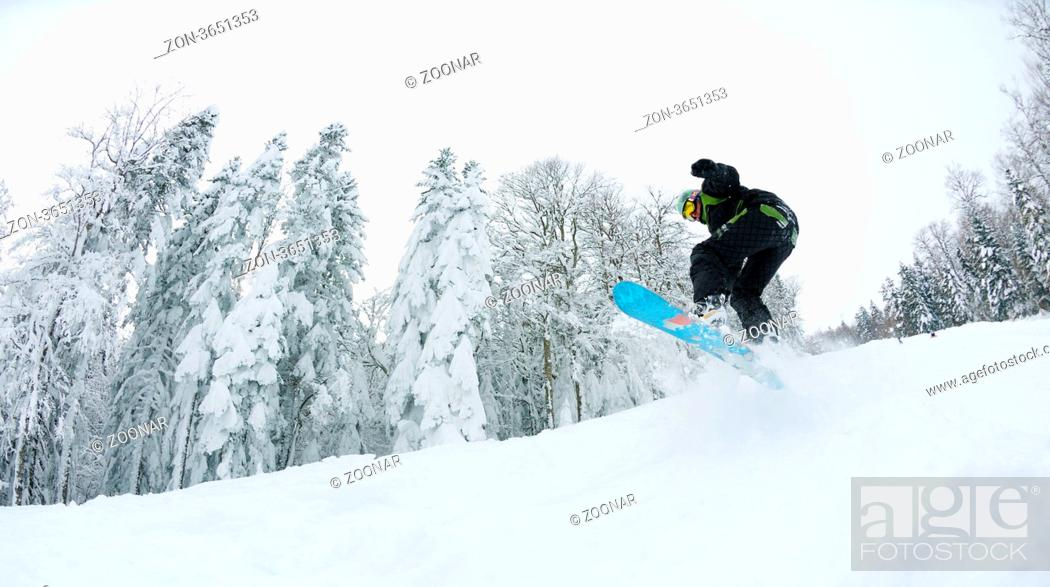 Stock Photo: Snowboarder doing a jump and free ride on powder snow at winter season.