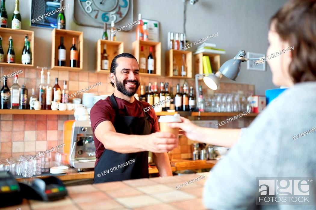 Stock Photo: small business, people, takeaway and service concept - happy man or waiter giving paper cup with hot drink to customer at coffee shop.
