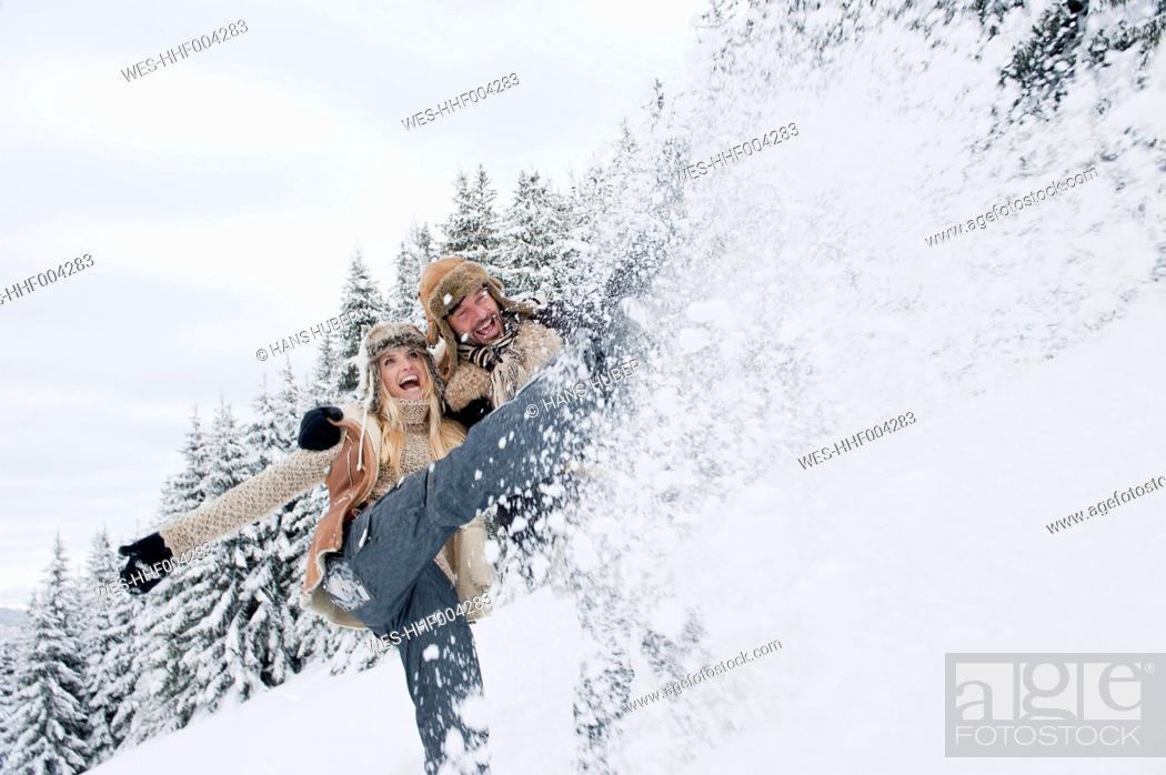 Stock Photo: Austria, Salzburg County, Couple splashing snow in snowy landscape,smiling.