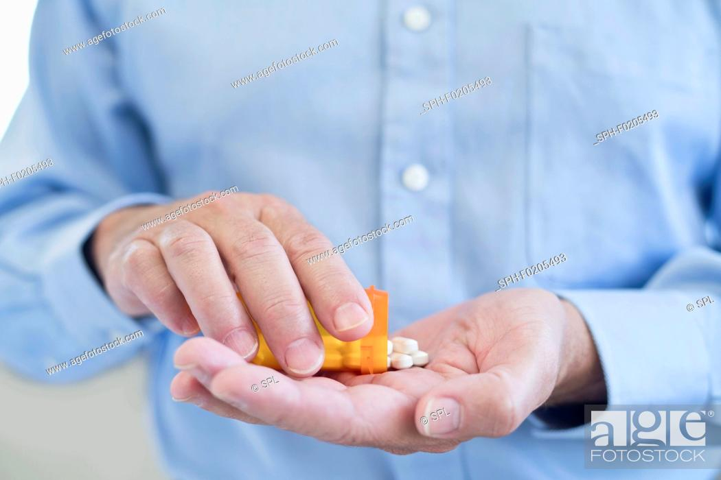 Stock Photo: Man pouring pills onto hand from bottle.