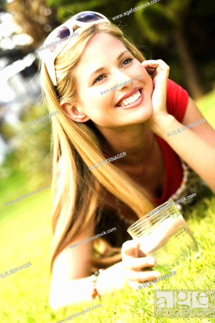 Stock Photo: Young smiling woman lying on grass, glass of water.