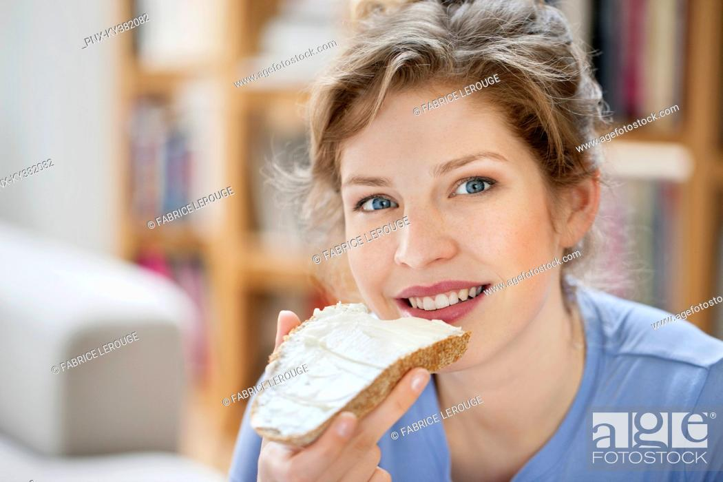 Stock Photo: Portrait of a woman eating toast with cream spread on it.