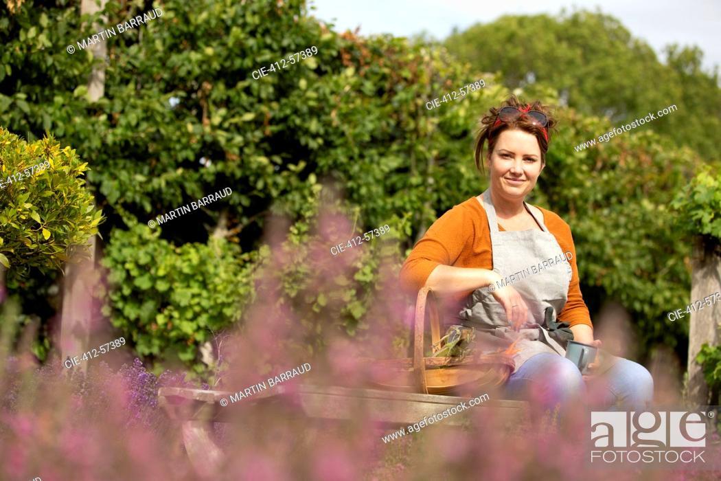 Stock Photo: Portrait happy woman taking a break from gardening in sunny garden.