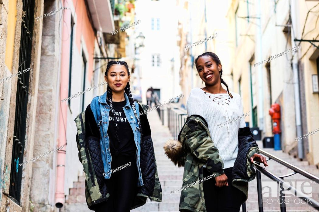 Stock Photo: Portugal, Lisbon, Two smiling young women walking outdoors.