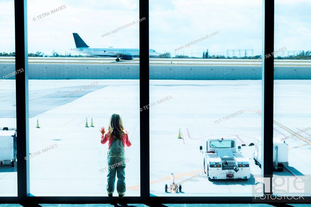 Stock Photo: Girl (2-3) looking through window at airport.
