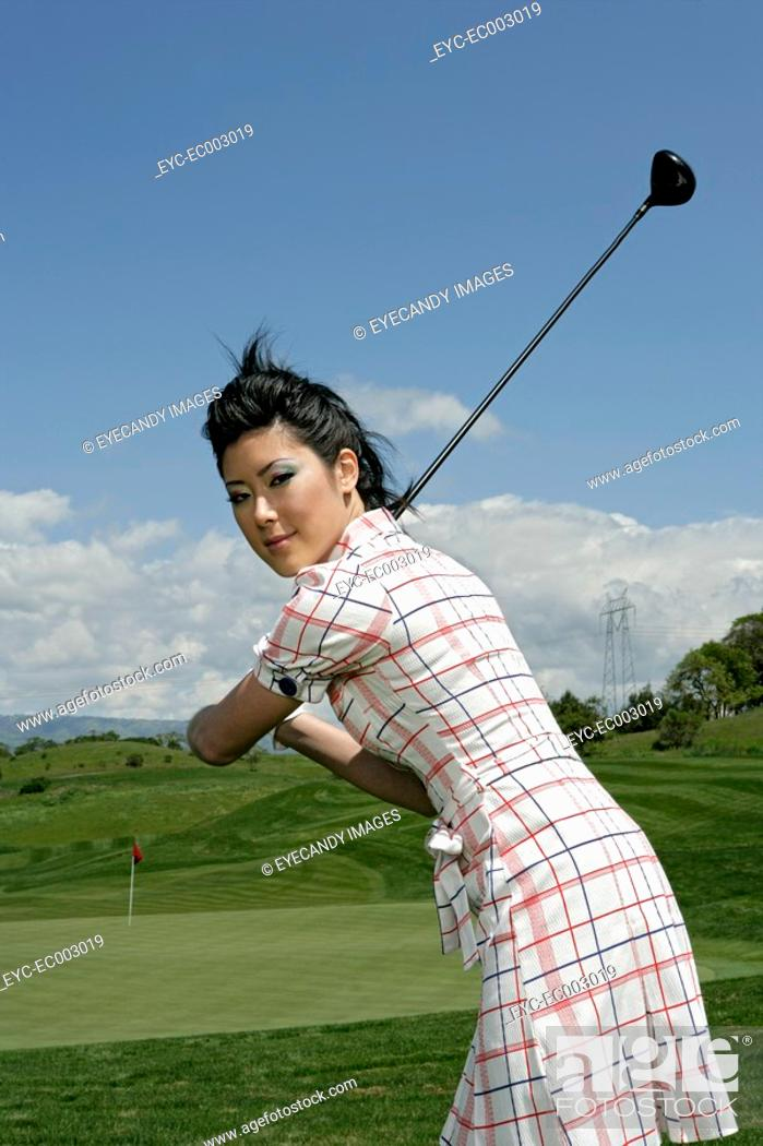 Stock Photo: Portrait of a young woman posing with a golf club.