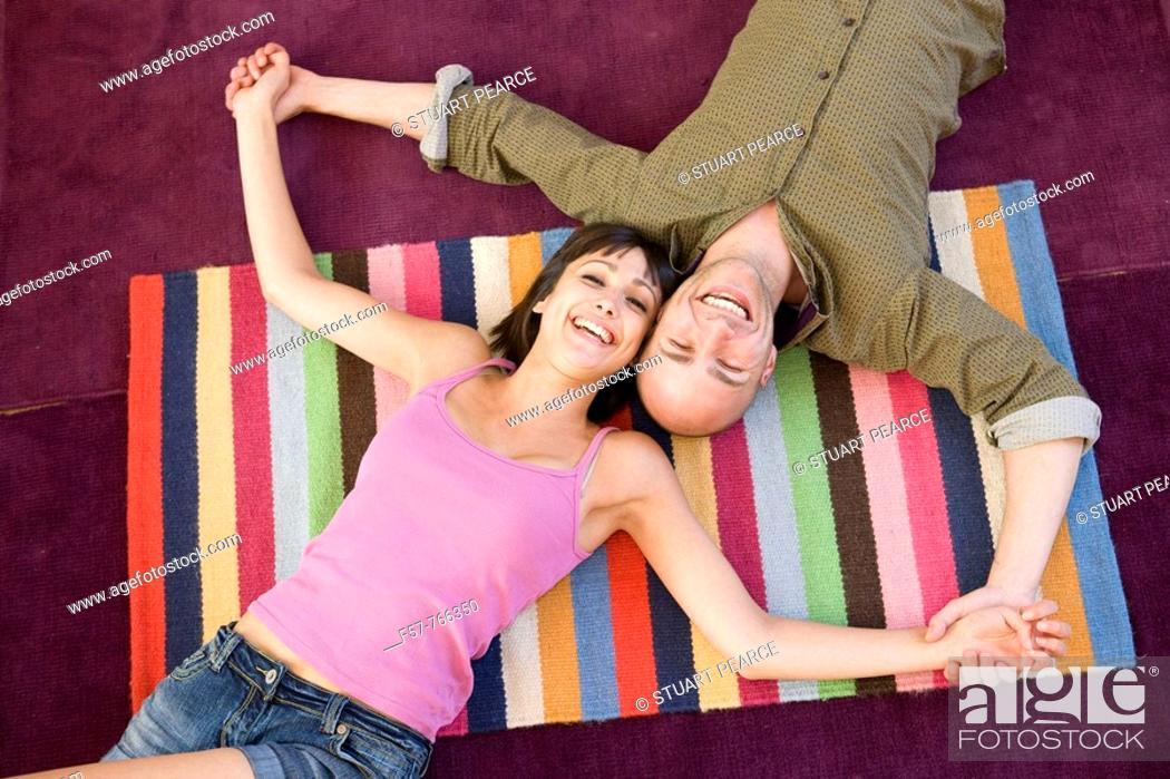 Stock Photo: Happy couple lying on the floor.