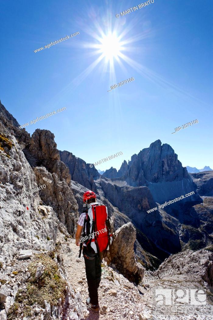Stock Photo: Climber on Mt Elferscharte or Forcella Undici in the Alpinisteig or Strada degli Alpini via ferrata, Mt Zwoelferkofel or Croda dei Toni in the back, Sexten.