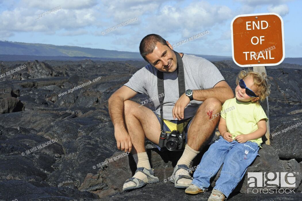 Stock Photo: Father with her doughter in the End of trail. Black lava mountains near the coast and highway Chain of Crater Road. Hawai'i Volcanoes National Park.