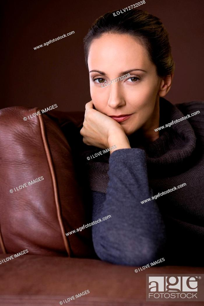 Stock Photo: Portrait of a mid adult woman sitting in an armchair.