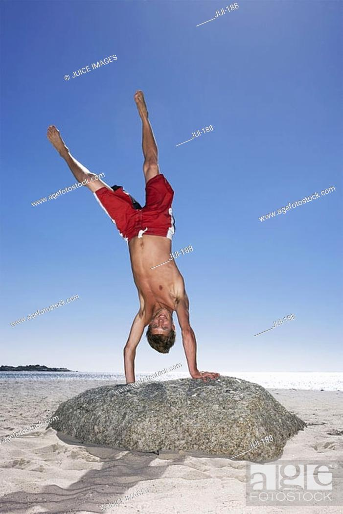 Stock Photo: Teenage boy 17-19 in red swimming shorts doing handstand on top of beach rock, smiling, portrait.