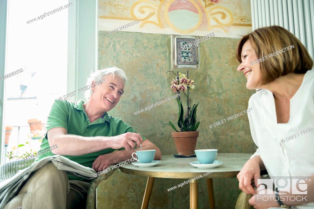 Imagen: Couple having coffee together, smiling.