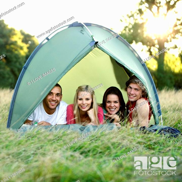 Stock Photo: Four young people lying in a tent, looking at camera.