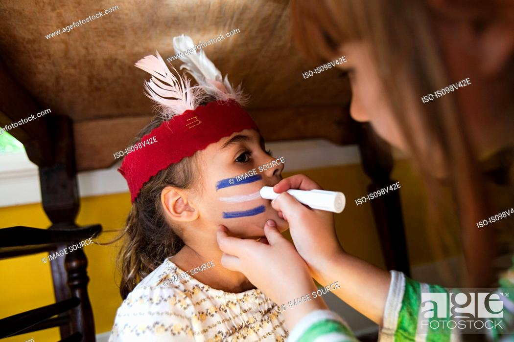 Stock Photo: Girl putting Native American face paint on another girl.