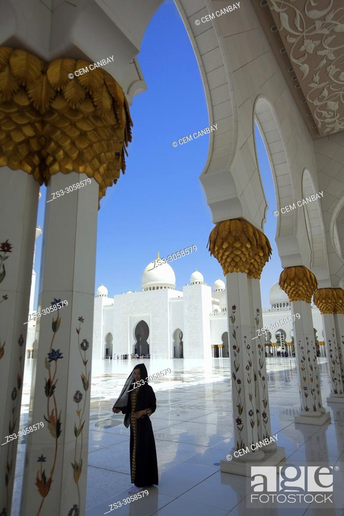 Stock Photo: Visitor with headscarf between the gilded columns of Sheikh Zayed Bin Sultan Al Nahyan Mosque, Abu Dhabi, United Arab Emirates, Middle East.