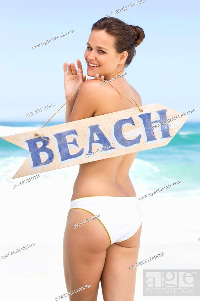Stock Photo: Rear view of a woman holding a BEACH signboard.