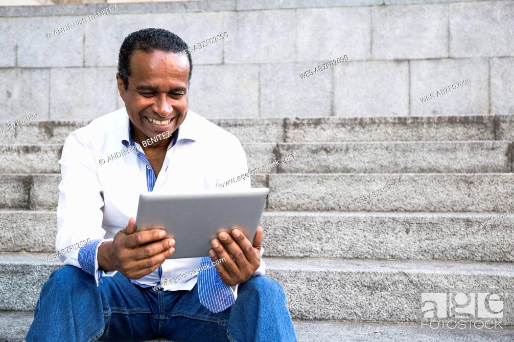 Stock Photo: Portrait of smiling man sitting on stairs looking at tablet.