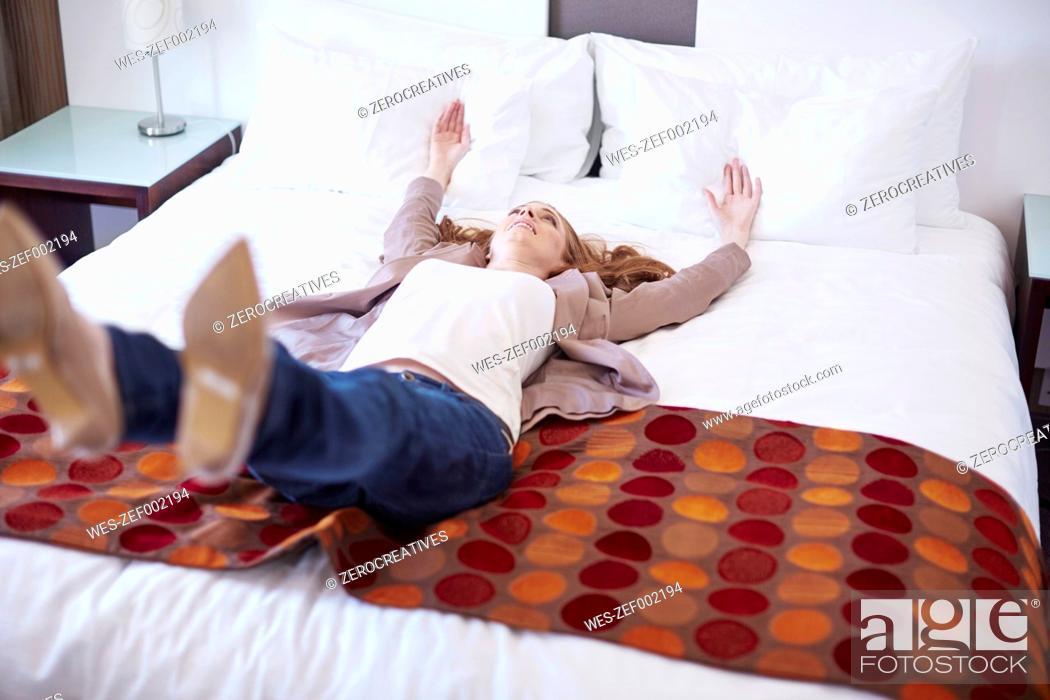 Stock Photo: Happy woman falling backwards on hotel bed.