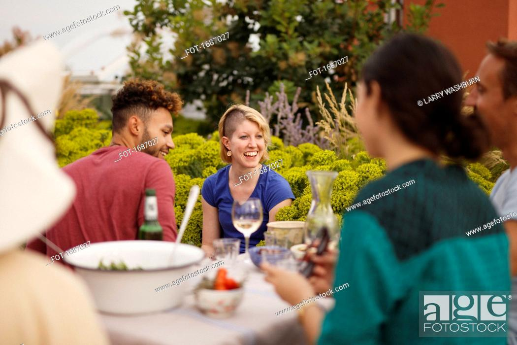 Imagen: Happy male and female friends sitting at outdoor table on patio.