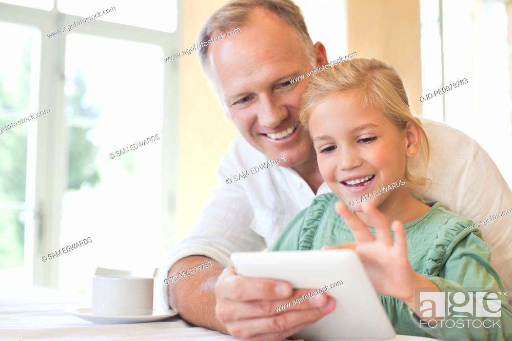 Stock Photo: Father and daughter using digital tablet.