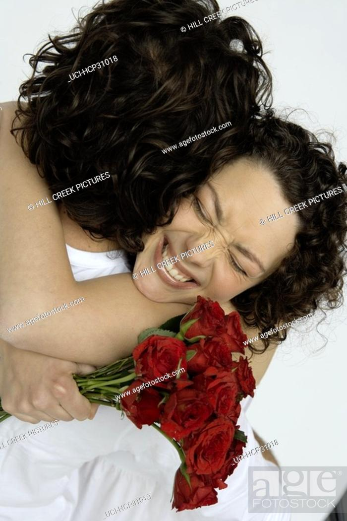 Stock Photo: Young man embracing young woman with bouquet of roses.