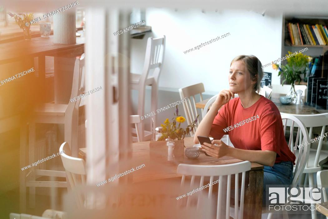 Stock Photo: Young woman with cell phone sitting at table in a cafe.