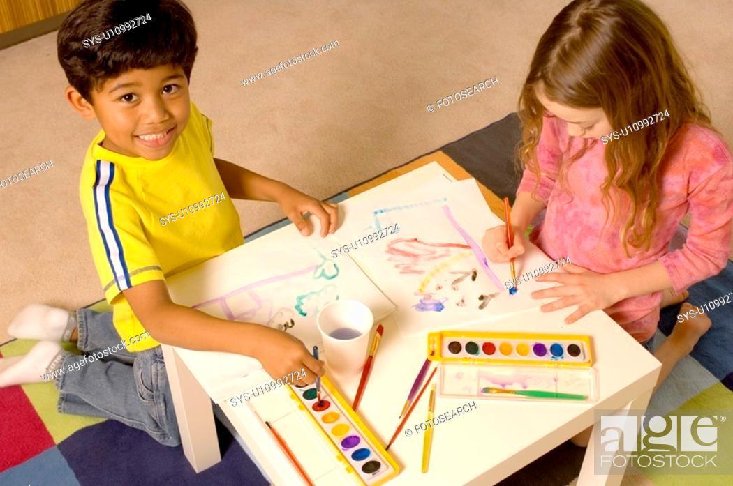 Stock Photo: Portrait of Hispanic boy and Caucasian girl painting.