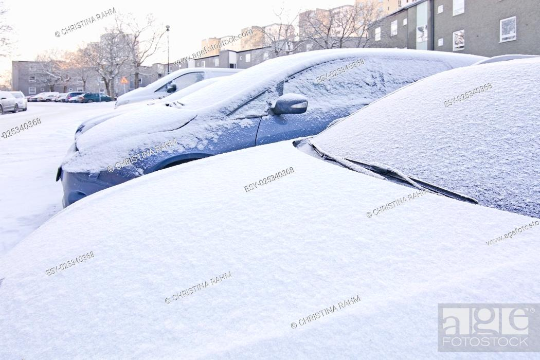Stock Photo: Snow and ice covers on parked cars outside in Sweden in December.