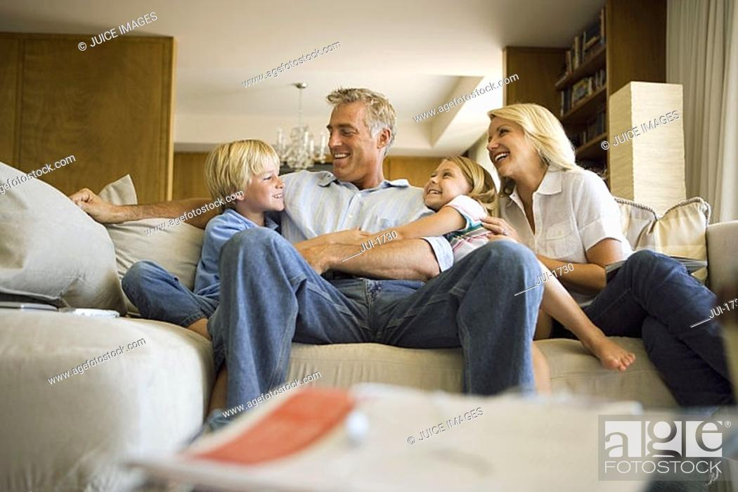 Stock Photo: Two generation family relaxing on sofa at home, smiling.