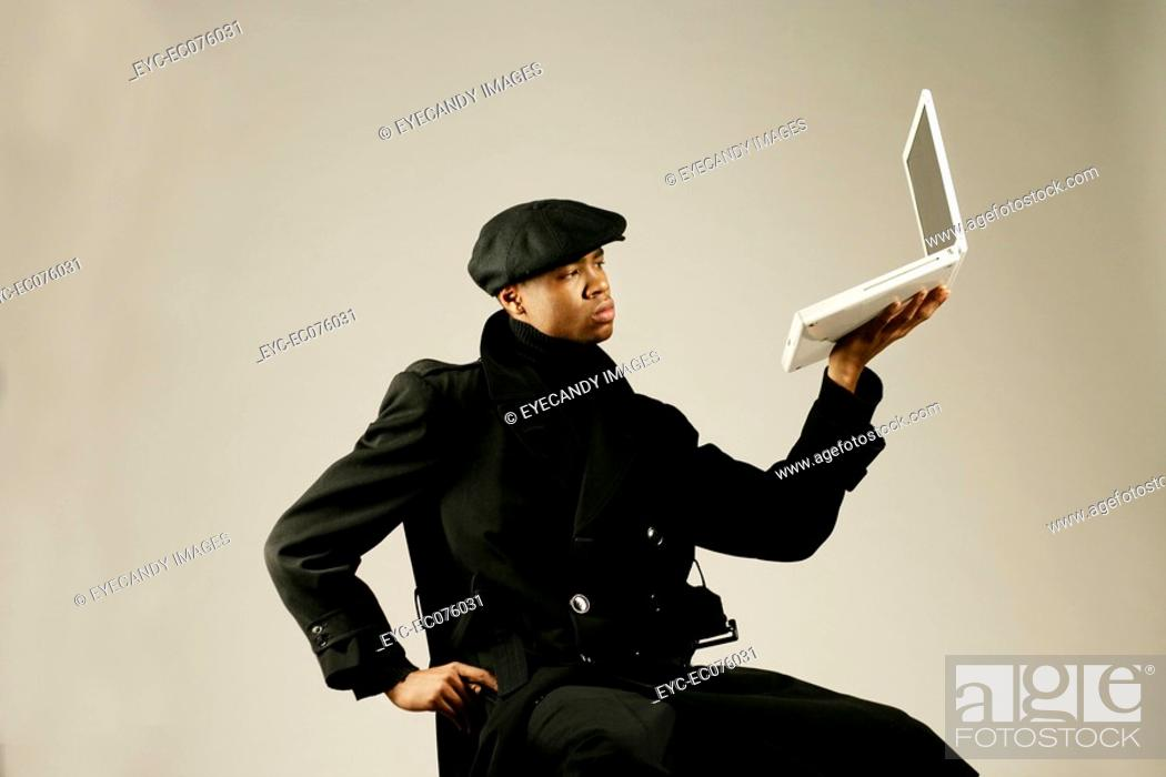 Stock Photo: Young African American man holding laptop, studio shot.