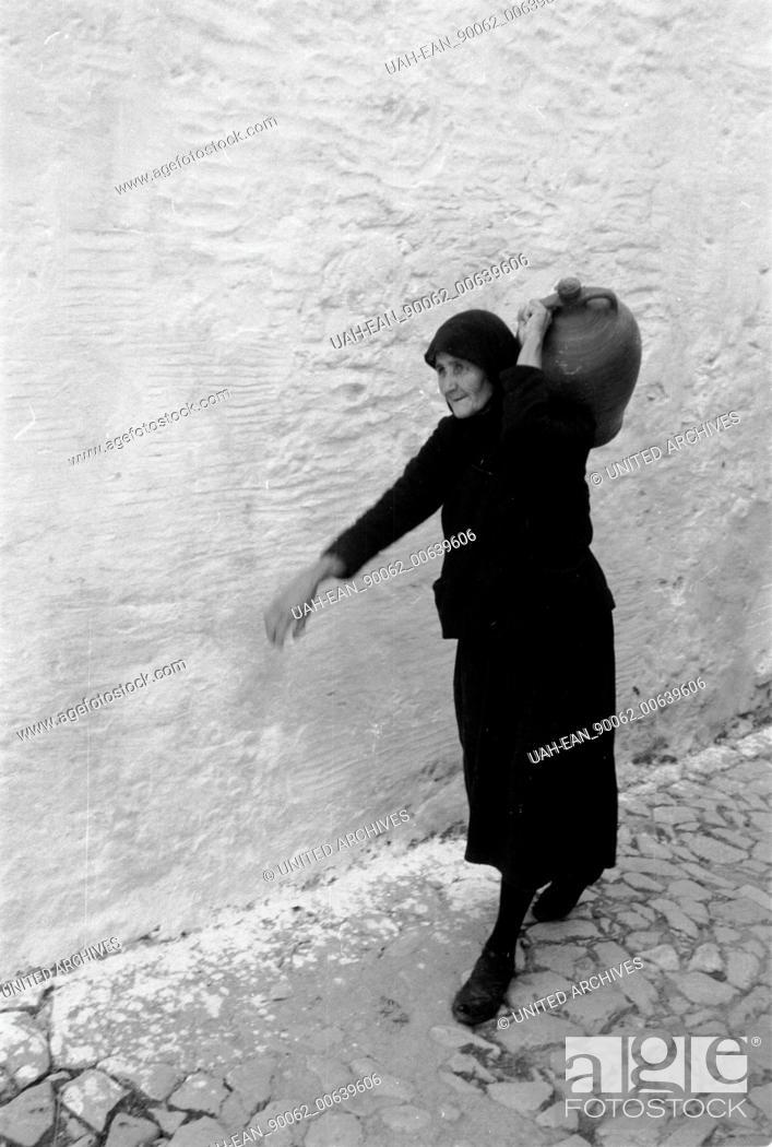 Stock Photo: Travel to Greece - Greece - old woman from Mykonos island, Cyclades. Image date circa 1954. Alte Frau trägt einen Krug auf der Insel Mykonos, Griechenland 1954.