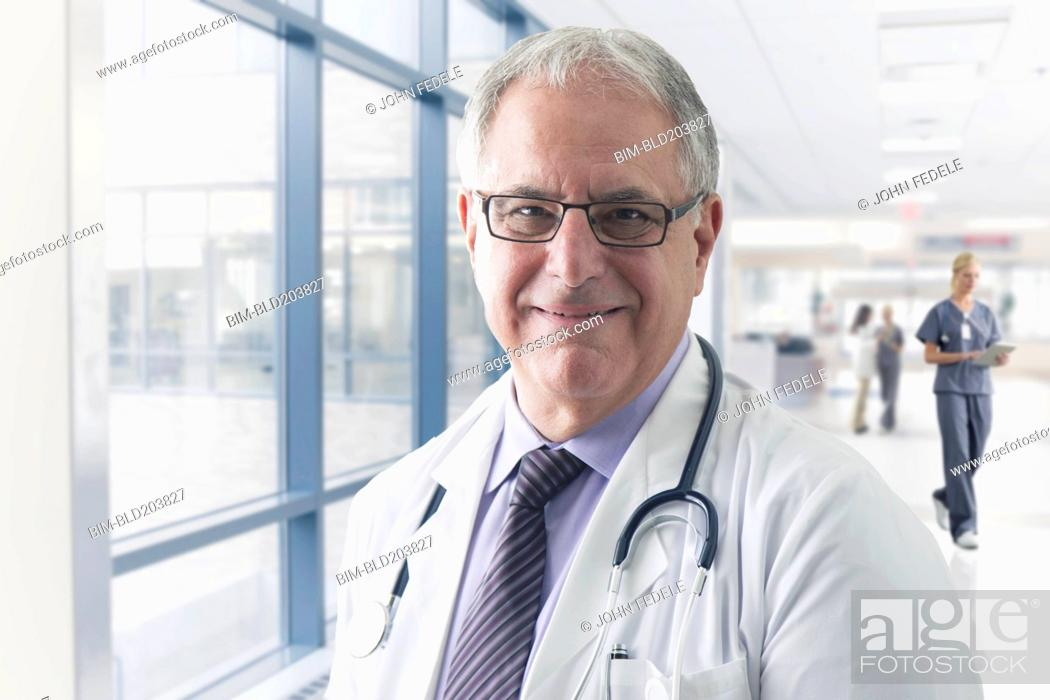 Stock Photo: Caucasian doctor smiling in hospital.